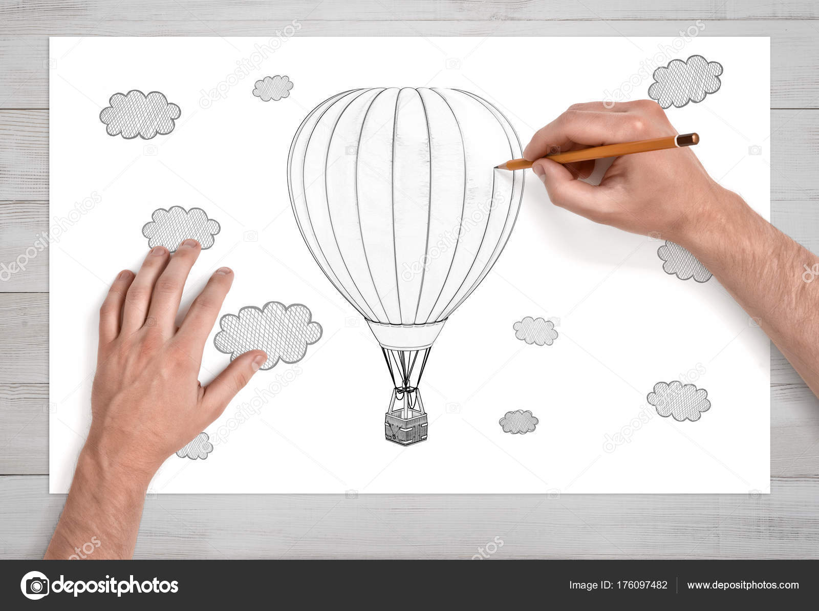 Male hands drawing a hot air balloon among the clouds with a pencil on a white