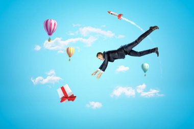 Businessman reaching to gift box with hot air balloons and silver red space rocket in the air on blue background