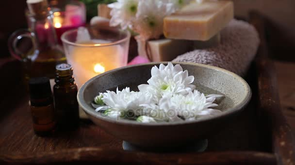 Spa set with bowl and white flowers and burning candles