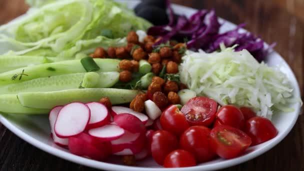 Přidání omáčka zálivku na salát sortiment zeleniny na talíři