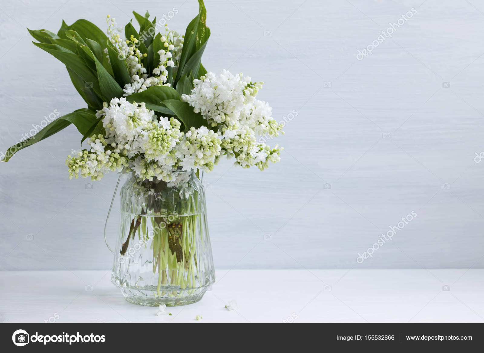 Spring white lilac and lily of the valley bouquet in a vase on w spring white lilac and lily of the valley bouquet in a vase on white board photo by marrakeshh reviewsmspy