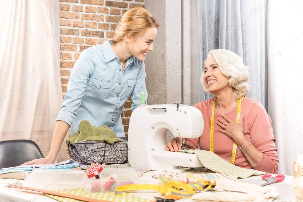 Senior woman and girl sewing