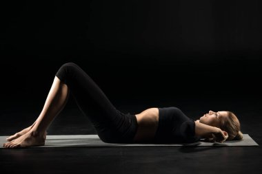 Woman lying on yoga mat