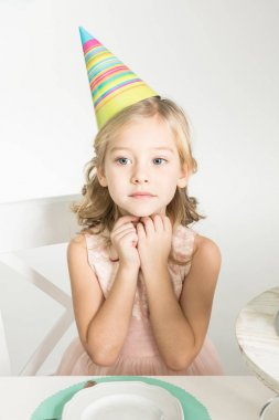 Cute little girl in party hat sitting at festive table isolated on white stock vector