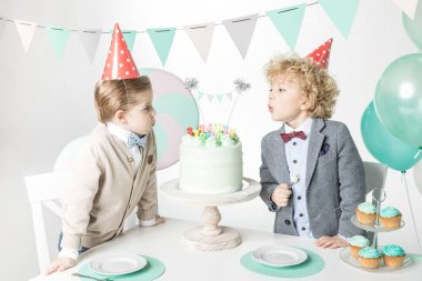 Boys blowing candles on cake