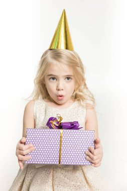Surprised little girl in cone hat holding birthday present isolated on white stock vector