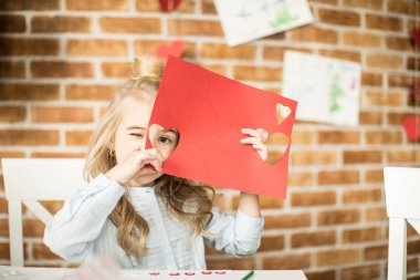 Girl holding red paper