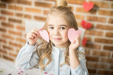 Girl holding paper hearts