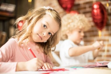 Beautiful little girl drawing at the table with red pen stock vector