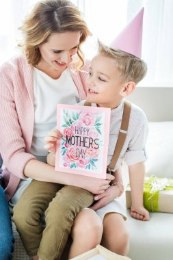 Mother and son holding greeting card