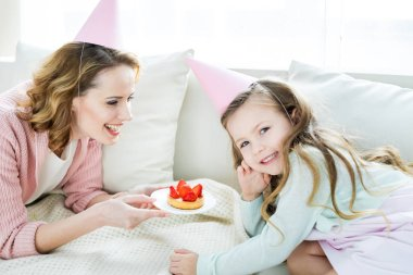 Mother and daughter with strawberry cake