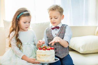 Siblings holding cake