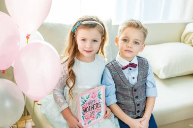 Siblings holding Mothers Day card