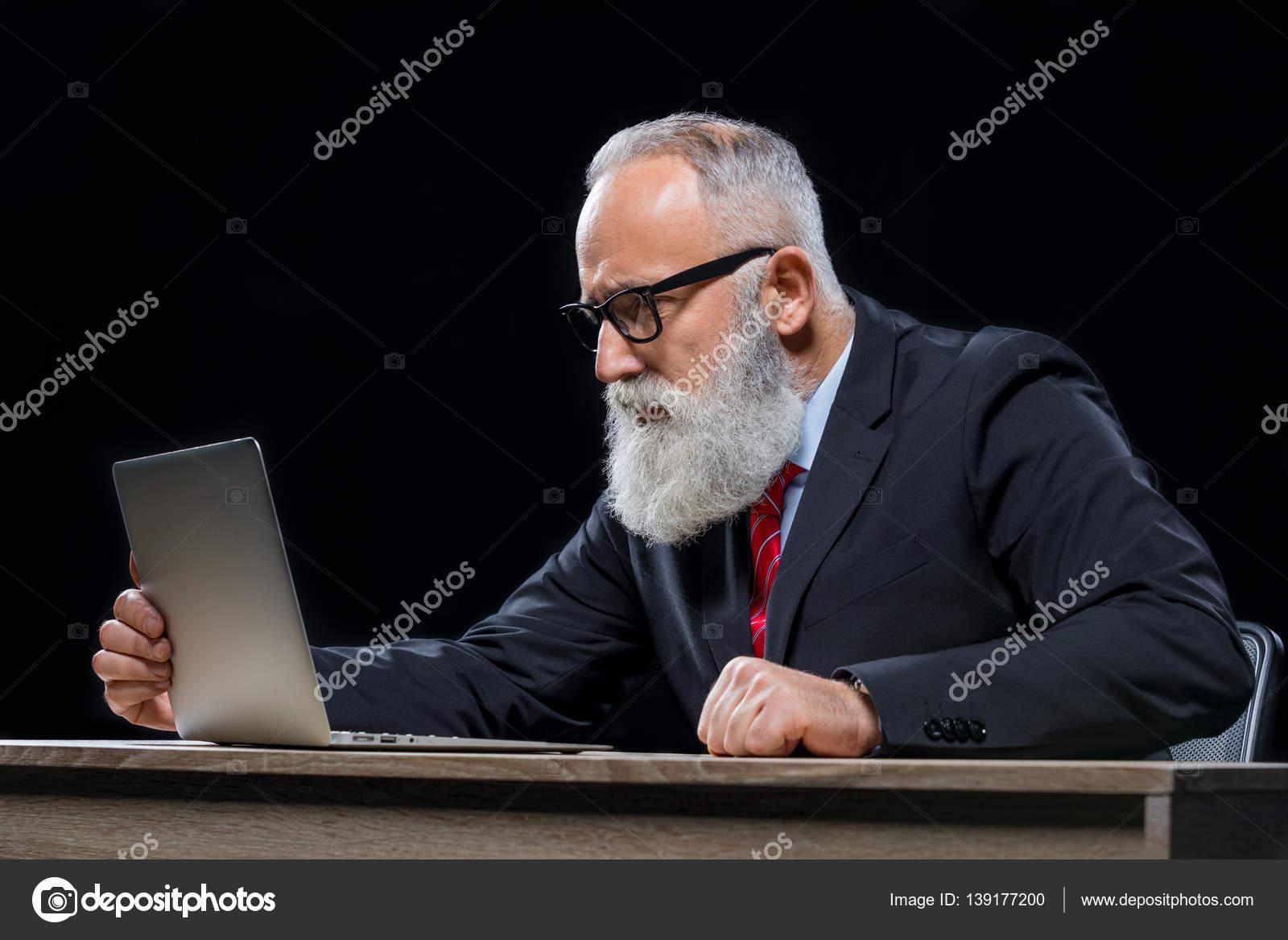 senior homme d 39 affaires avec ordinateur portable photographie olgazakrevskaya 139177200. Black Bedroom Furniture Sets. Home Design Ideas