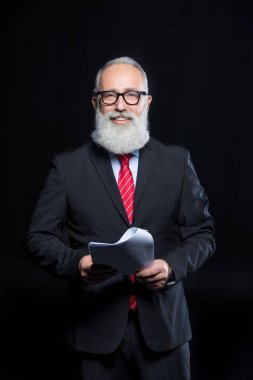 Senior bearded businessman in eyeglasses holding documents and smiling at camera isolated on black stock vector