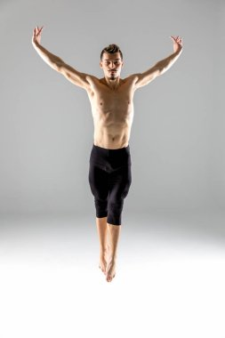 Young shirtless man performing contemporary dance movement and looking at camera stock vector