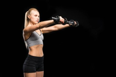Young blonde woman in sportswear exercising with dumbbells isolated on black stock vector
