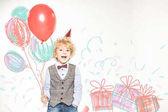 Junge mit Hütchen und Luftballons