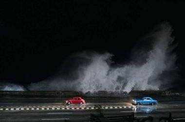 driving cars on flooded road in Havana, Cuba