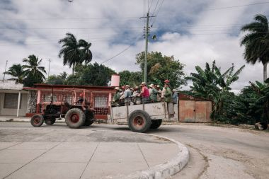 Sancti Spiritus, Cuba - January 10, 2017: tractor driving with old cart filled of locals