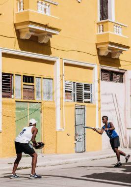 Havana, Cuba - January 22, 2017: two teenagers playing baseball on street