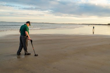 Man using a metal detector to search for lost treasure on a beach.