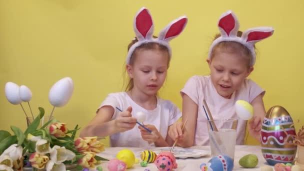 Zaostřené sestry s králičí uši stojící u stolu s paletou a kyticí tulipánů zbarvení vejce pečlivě při přípravě na velikonoční oslavu proti žlutému pozadí