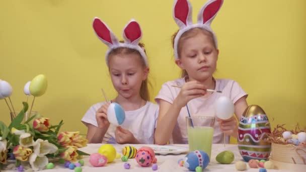 Fókuszált nővérek nyuszifül áll asztal mellett paletta és csokor tulipán színező tojás óvatosan, miközben készül a húsvéti ünnepség sárga háttér