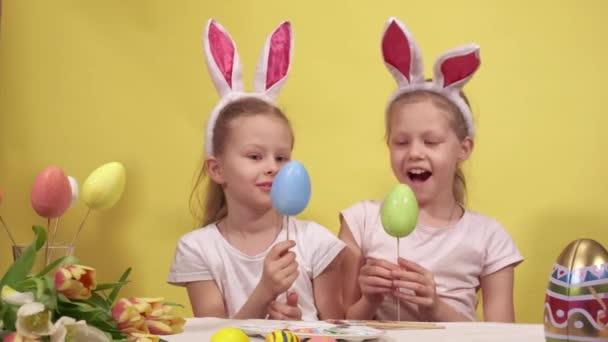 Boldog kislányok nyuszifül mosolygós és demonstráló festett tojások botokon, miközben ül az asztalnál, és készül a húsvéti ünnepség sárga háttér