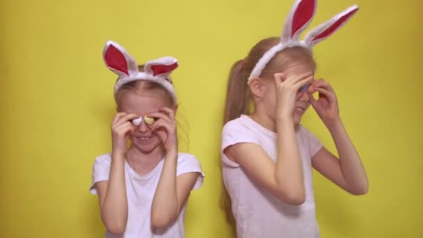 Cute sisters with bunny ears keeping colorful quail eggs near eyes and showing tongues while preparing for Easter celebration against yellow background