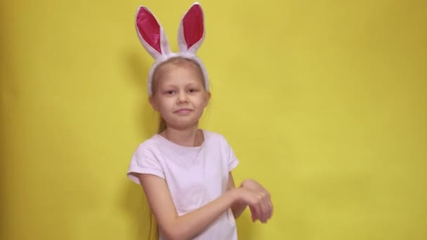 Cute little girl with bunny ears looking at camera and jumping while pretending to be rabbit during Easter celebration against yellow background