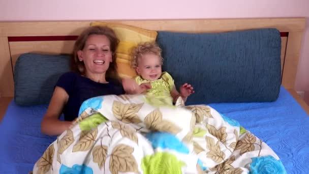 Smějící se matka s batole dívka si hraje v posteli