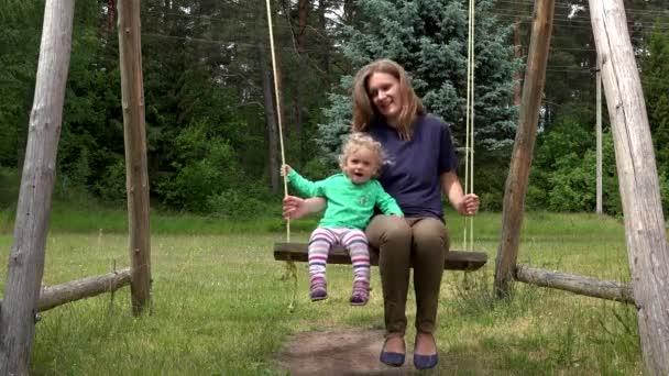 Šťastné dítě dívka a matka houpat se v parku hřiště