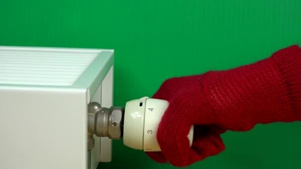 Hand mit Handschuh zur Anpassung der Wohntemperatur mit Heizkörper-Thermostat-Griff.