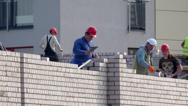 Builder men team with protective helmets laying white bricks on new house wall