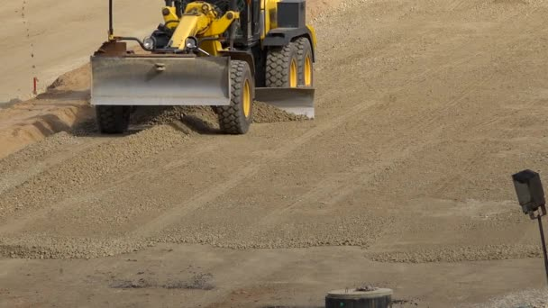 Grader machine leveling gravel rubble on road construction site