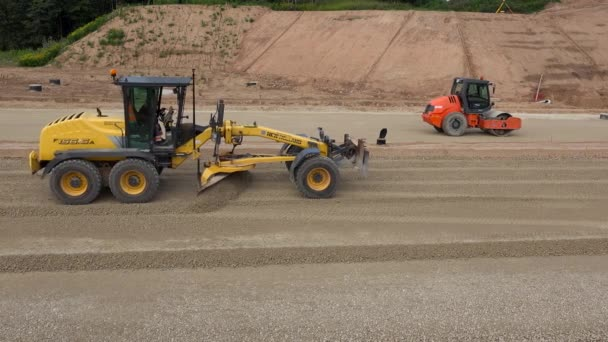 Grader machine and roller leveling rubble stones on new road construction site