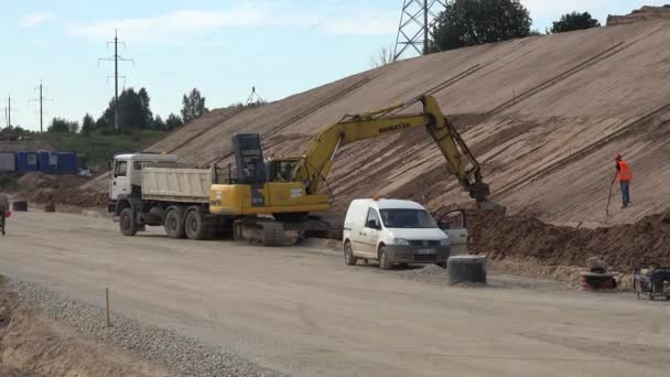 Excavator digging sand and roller machine leveling new highway layers