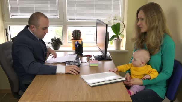 Woman with baby signing divorce documents at lawyer office. 4K