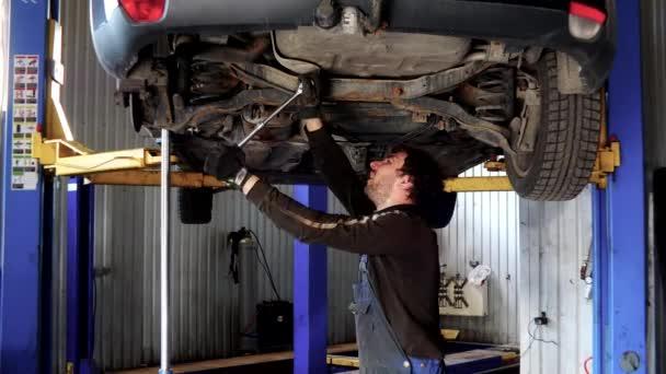 Autó garázsban alatt dolgozó férfi autószerelő