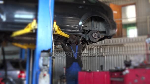 auto mechanik pracovník opravu suspenze zdvižené automobilu na opravu garáže