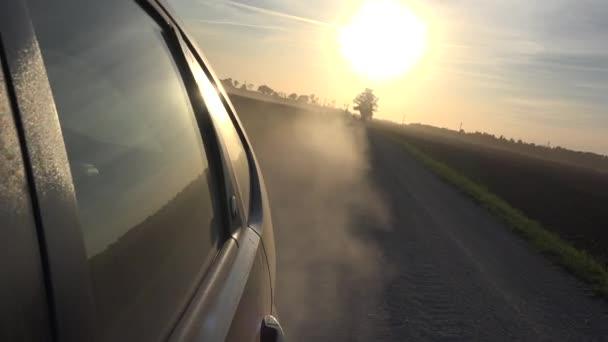 Prach z automobilových kol automobilů jízdy na venkovských štěrkové silnici večerní slunce v obloze. 4k