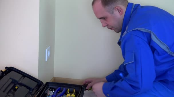 Operaio elettricista fine lavoro e fuori tutti gli strumenti nella casella