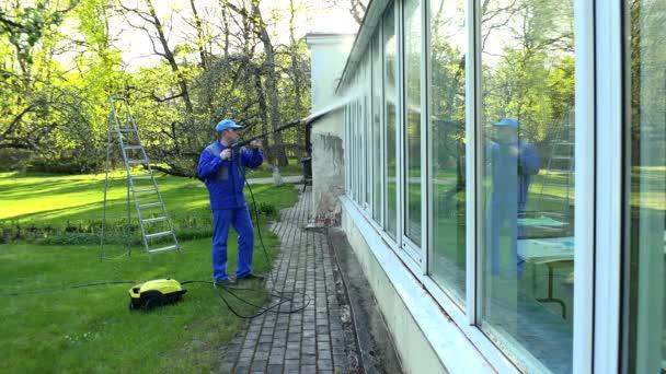 profesionální pracovník čištění špinavá okna s vysokotlakým vodním paprskem