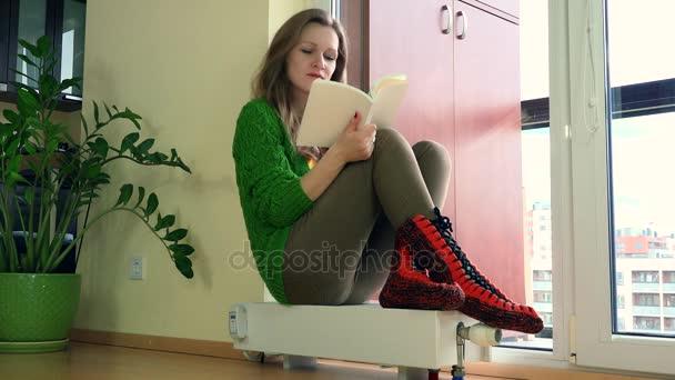 Kniha čtení zmrazené žena sedí na radiátor a nastavení termostatu