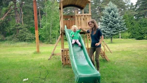Femme De Baby Sitter Aider Tout Petit Enfant A Glisser Vers Le Bas