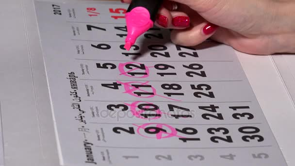 Female hand planning working days with pink marker on calendar