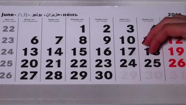 Ženská ruka odtrhnout kalendář papírové stránky uplynulého roku 2016