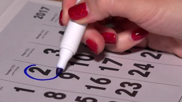 Woman hand circle and cross days on paper calendar