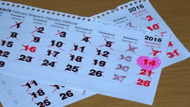 Stránky teared kalendáře padají na dřevěný povrch